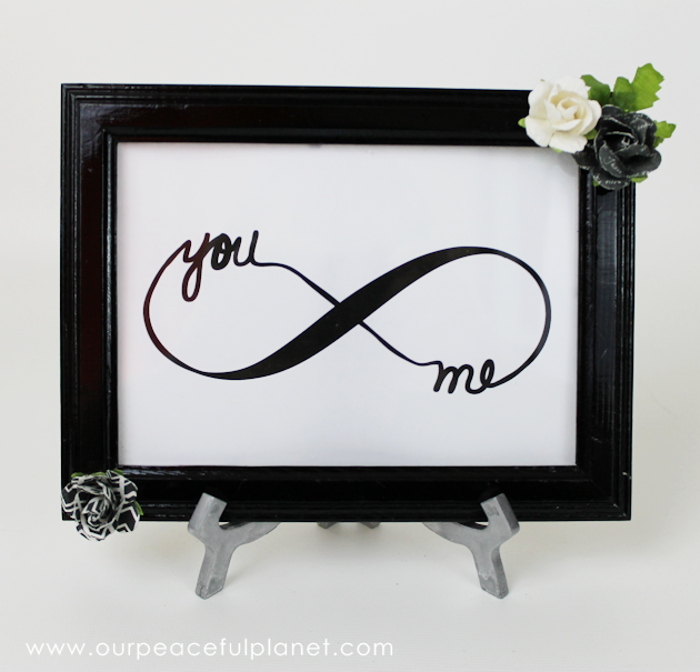 Free Couples Infinity DIY Bedroom Decor Looking for a quick and easy piece of DIY bedroom decor? Download our free couple's infinity symbol, frame it and add some flowers. How's that for easy? We took it even further and used an old frame we had and spiced it up a bit and also painted a easel. It turned out lovely and sits in our bedroom. The download comes in three sizes so you can choose and frame as desired or also mat it. DIY Bedroom Decor Supplies Free artwork download below (4×6 5×7 & 8×10) Frame Extras (flowers etc.) Glue gun Instructions Not that many are needed but I'll show you what I did. I'm sure a lot of you will use a frame as it is. But I enjoyed upcycling one I had. Cut out your symbol size of choice. I used the 5×7. I found an old frame to upcycle. I spray painted it gloss black. Then I added my infinity symbol.I was going to make some mini spiral rose diy paper flowers but I had these in my craft supplies and they matched my bedroom and the frame so I decided to use them. I glued my flowers on opposite corners of my frame. I also had an old tripod. Since I wanted to set my frame on a shelf I used it.I wanted it to be silver though so I spray painted it.