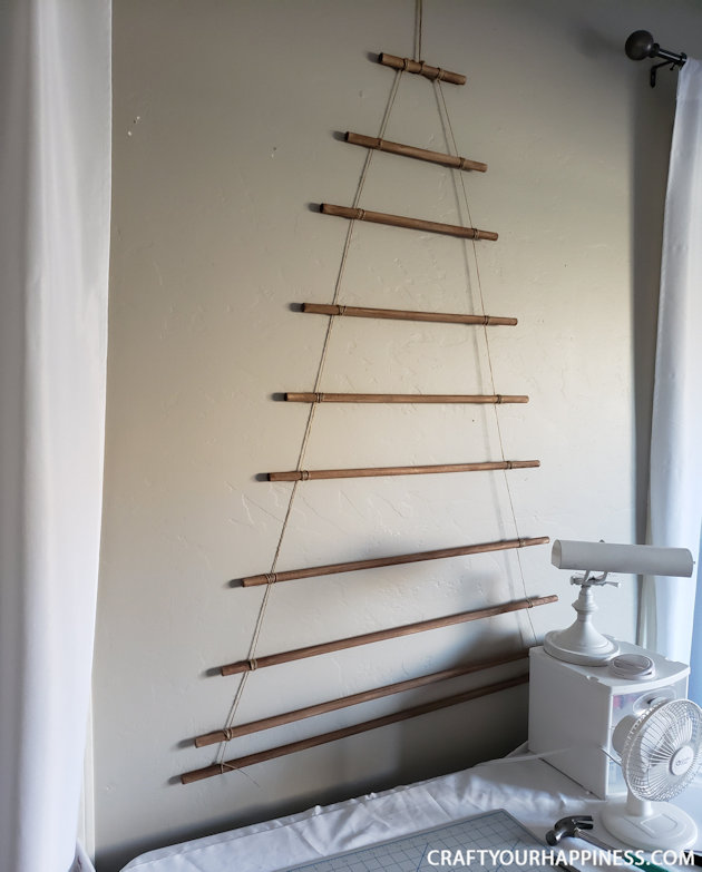 This easy DIY hanging wall Christmas tree made from dowels (or branches) is perfect if you're on a budget or you have very little space for a normal tree.